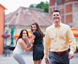 2 women laughing on walking man